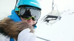 Woman skier in goggles goes up in chairlift to ski route. Stock Footage