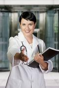 smiling medical doctor with stethoscope. over hospital background - stock photo