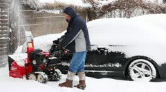 Man cleans snow near house by snowplow at winter Stock Footage