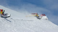 Three snowplow cleans snow on mountain road in sunny weather Stock Footage