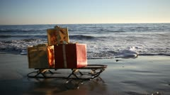 Christmas gifts on a sled on the beach in Malibu, Los Angeles in the USA Stock Footage