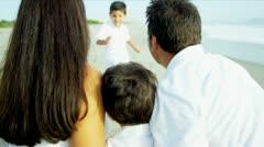 Hispanic kids embracing with parents on sandy beach - stock footage