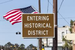 Entering historical district road sign with american flag Stock Photos