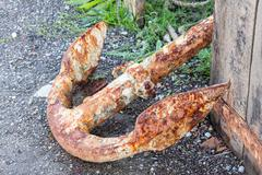 Old rusty anchor on dockside Stock Photos