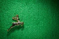 Golden raindeer jumping on green carpet. Stock Photos