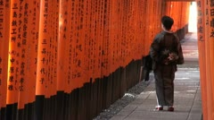 Geisha lady walks through vermillion torii gates in Kyoto, Japan Stock Footage