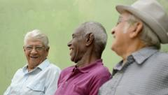 Happy seniors, portrait of three old men laughing and talking in park - stock footage