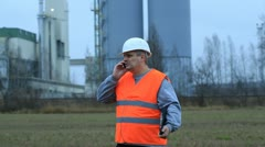 Foreman talking on the cell phone near the factory Stock Footage