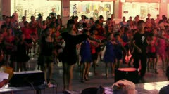 Dancing Chinese children crowd in the square at night. Stock Footage