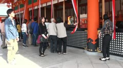 People praying at the Fushimi Inari temple in Kyoto, Japan Stock Footage