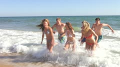 Group of teenage friends stand in the sea before running onto beach Stock Footage
