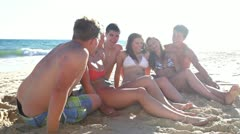 Group of teenage friends sitting on beach in swimsuits talking and laughing Stock Footage