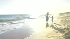 Little girl holds mother's hand as they skip through the surf and then past Stock Footage