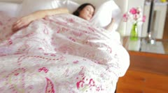 Camera tracks along bed to sleeping woman snuggled under duvet Stock Footage