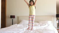 Young girl bounces excitedly on bed looking at camera Stock Footage