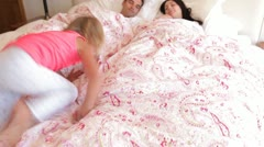 Parents sleeping peacefully in bed before daughter jumps onto bed and bounces Stock Footage