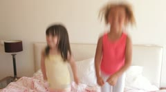 Two young girls bouncing excitedly on bed looking at camera - stock footage