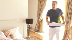 Stock Video Footage of Man walks into bedroom and places tray with breakfast in front of woman in bed