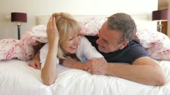 Senior husband and wife snuggled under duvet chatting together Stock Footage