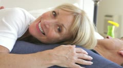 Senior woman lying on husbands chest and looking into camera Stock Footage