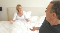 Husband sits on the end of bed arguing with wife who is still in bed Stock Footage