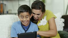 A mother and son spending time together and using a digital tablet - stock footage