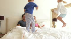 Boy and girl jumping on parents bed Stock Footage