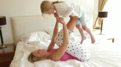 Mother lying on bed and supporting daughter on feet - stock footage