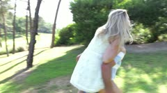 Woman riding on man's back as they spin and walk along country path - stock footage
