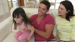 Parents sit on sofa with little girl as father bounces her up and down Stock Footage