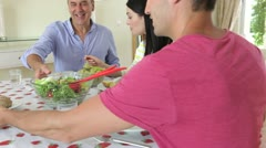 Couples seated around dining table serving food Stock Footage