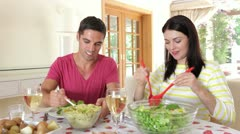 Couple seated around dining table serving one another - stock footage