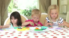 Group of three children sit around table concentrating on painting with fingers - stock footage