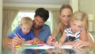 Father helping son and mother help daughter as they work on picture with pens Stock Footage