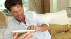 Man lying on sofa with digital tablet laughing and reacting Stock Footage