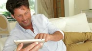 Stock Video Footage of Man lying on sofa with digital tablet laughing and reacting