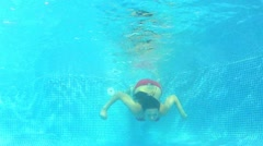 Underwater view as woman swims towards camera and waves as she blows bubbles Stock Footage