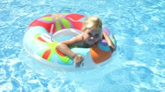 Girl in inflatable rubber ring paddles towards camera before moving away Stock Footage