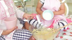 Two girls sitting at kitchen table mixing ingredients in bowl with wooden spoon Stock Footage