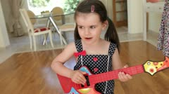 Daughter plays toy guitar and sings whilst mother plays drum - stock footage