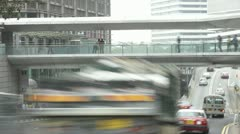 Traffic speeds along road as commuters use pavement and walkway Stock Footage