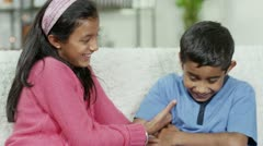 A young girl tickles her brother and they both laugh Stock Footage