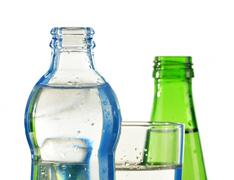glass and bottle of mineral water isolated on white - stock photo