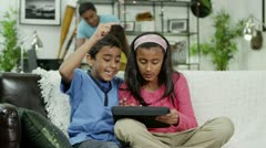 Young boy and girl playing on a digital tablet Stock Footage