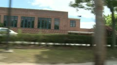 Driving passed brick building Stock Footage