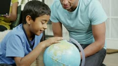 Father and son using a globe to look at countries around the world Stock Footage