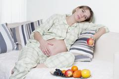 Pregnant woman with fruits Stock Photos
