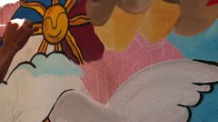 Mural painter draws sun Stock Footage