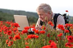 Stock Photo of photographer in poppy field