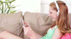 Teen Tween Headphones Laughing with Tablet Computer on Couch Medium Shot Stock Footage